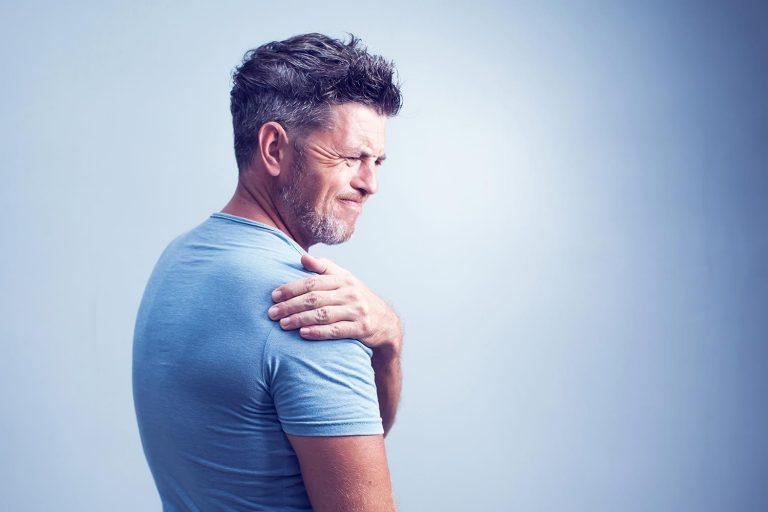 man in pain holding shoulder