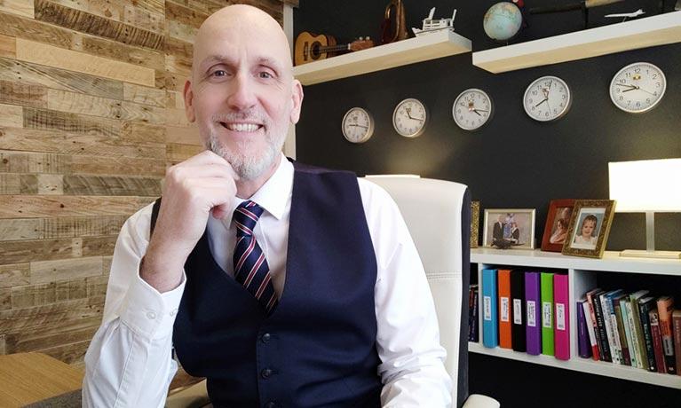 Smart man smiling at desk
