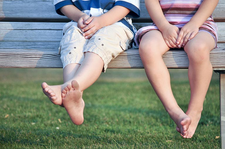 Childrens legs sitting on a bench