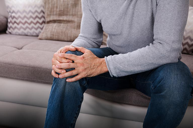 Man with knee pain sitting on sofa