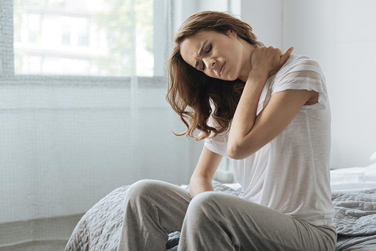 Woman on a bed holding her neck