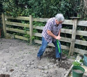 Chris digging with a spade in his garden following his operation