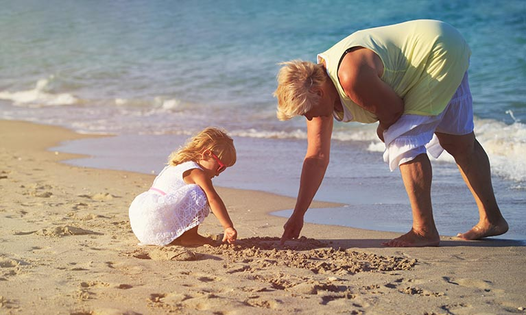 Lady on the beach playing with grand child